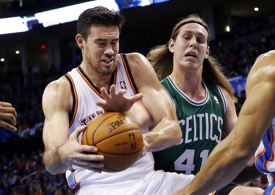 Photo - Boston Celtics center Kelly Olynyk (41) reaches in to try and knock the ball away from Oklahoma City Thunder forward Nick Collison in the second quarter of an NBA basketball game in Oklahoma City, Sunday, Jan. 5, 2014. (AP Photo/Sue Ogrocki)