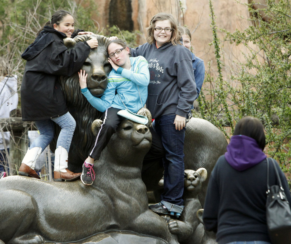Photo - Girls pose on a large bronze cat statue during ScienceFest at the Oklahoma City Zoo.