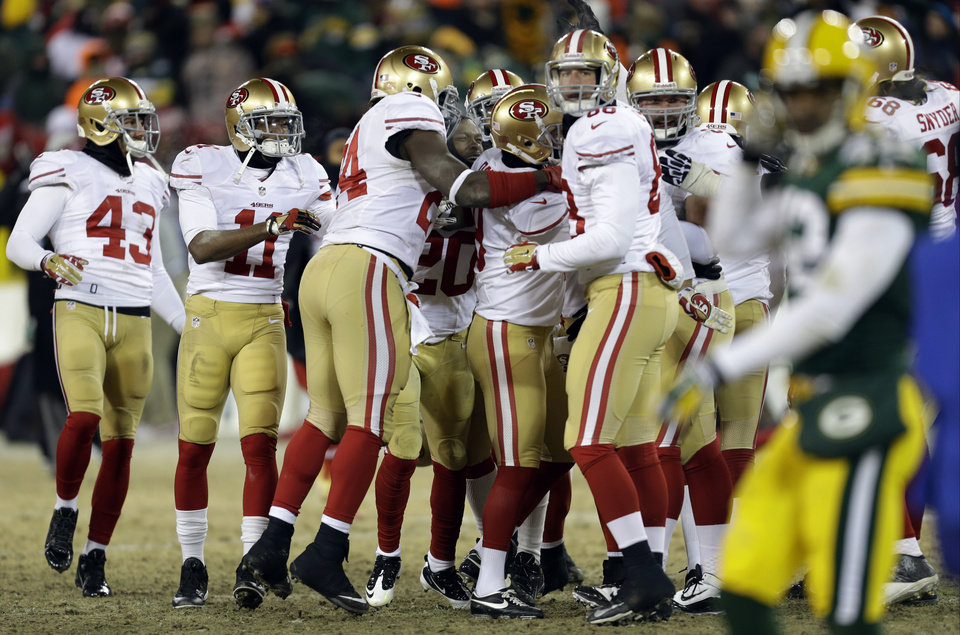 Photo - San Francisco 49ers players celebrates after San Francisco 49ers kicker Phil Dawson (9) kicks the game winning field goal during the second half of an NFL wild-card playoff football game, Sunday, Jan. 5, 2014, in Green Bay, Wis. The 49ers won 23-20. (AP Photo/Mike Roemer)