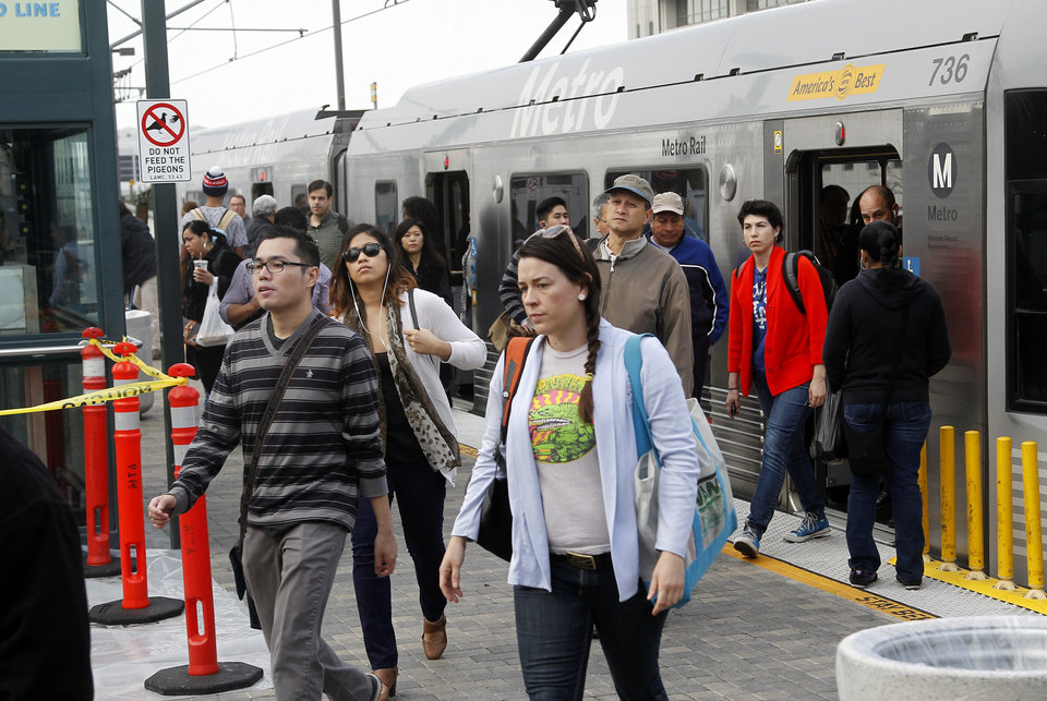 Photo - Pedestrians disembark from a train at Union Station Friday March 7, 2014 in Los  Angeles. Americans are boarding public buses, trains and subways in greater numbers than any time since the suburbs began to boom. Nearly 10.7 billion trips in 2013, to be precise, the highest number since 1956.  (AP Photo/Nick Ut)