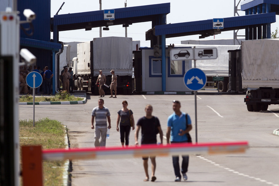 Photo - Trucks of the Russian aid convoy are searched at a Russian inspection zone inside a border control point with Ukraine in the Russian town of Donetsk, Rostov-on-Don region, Russia, Friday, Aug. 22, 2014. The first trucks of the Russian aid convoy crossed the Ukrainian inspection zone Friday morning. (AP Photo/Pavel Golovkin)