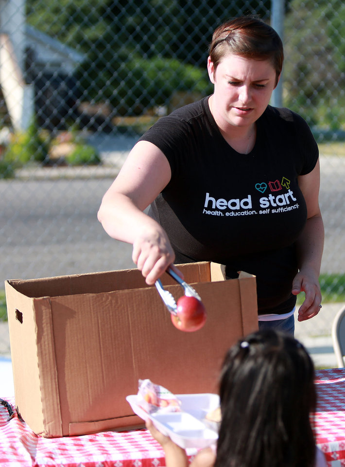 Photo -       Liz Guerrero, site supervisor, hands an apple to a child as part of her dinner outside of the Central Park Community Center in South Salt Lake on Friday, July 18, 2014. The dinner is part of the Salt Lake CAP summer food program, which offers free dinner to children at five locations in the valley, Monday through Friday.