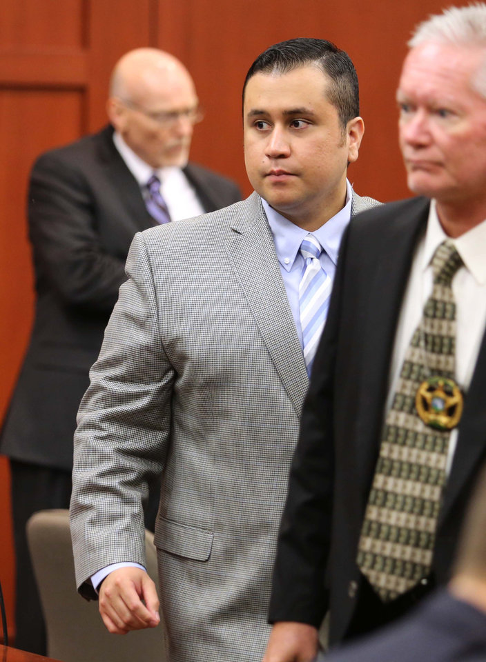 Photo - George Zimmerman, center, returns to the courtroom after a recess in Seminole circuit court during his trial, in Sanford, Fla., Wednesday, June 12, 2013. Zimmerman has been charged with second-degree murder for the 2012 shooting death of Trayvon Martin.(AP Photo/Orlando Sentinel, Joe Burbank, Pool)