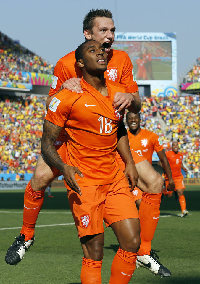 Photo - Netherlands' Leroy Fer, front, is congratulated by his teammate Stefan de Vrij after scoring the opening goal during the group B World Cup soccer match between the Netherlands and Chile at the Itaquerao Stadium in Sao Paulo, Brazil, Monday, June 23, 2014. (AP Photo/Frank Augstein)