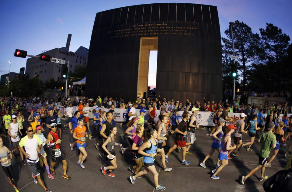 Photo - In this photo taken with a fisheye lens, runners begin the Oklahoma City Memorial Marathon going south on N. Harvey Ave. in downtown Oklahoma City, Sunday, April 24, 2016. Photo by Nate Billings, The Oklahoman