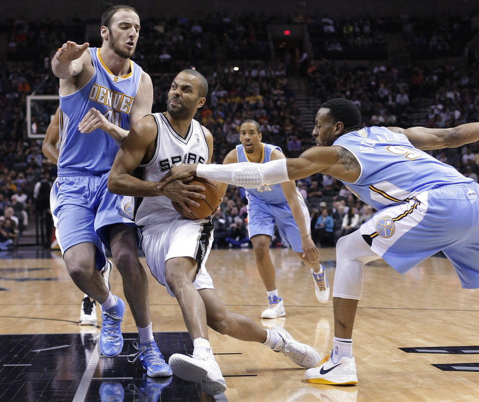 San Antonio Spurs\' Tony Parker, center, of France, drives between Denver Nuggets defenders Kosta Koufos (41) and Andre Iguodala (9) during the first half of an NBA basketball game, Wednesday, March 27, 2013, in San Antonio. (AP Photo/Eric Gay)