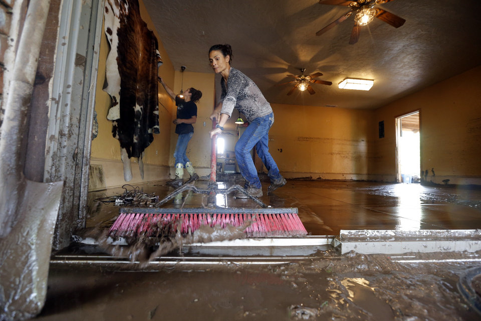 Photo - Cheryl Self sweeps mud from the Easter home after the West Cache Creek overflowed and flooded the area, Sunday, May 24, 2015, in Cache, Okla., Photo by Sarah Phipps, The Oklahoman