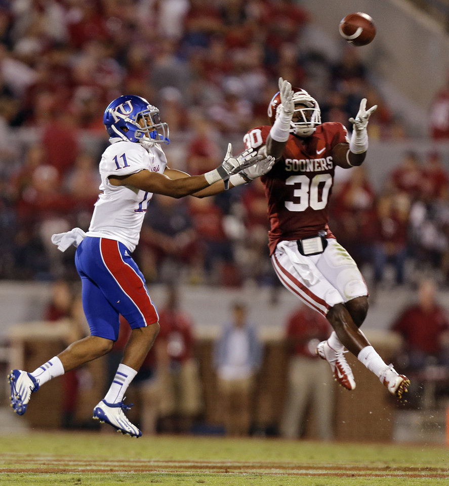 OU\'s Javon Harris (30) makes an interception in front of KU\'s Tre\' Parmalee (11) during the college football game between the University of Oklahoma Sooners (OU) and the University of Kansas Jayhawks (KU) at Gaylord Family-Oklahoma Memorial Stadium on Saturday, Oct. 20th, 2012, in Norman, Okla. Photo by Chris Landsberger, The Oklahoman