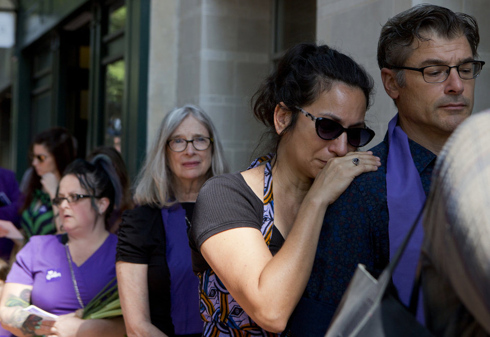 "Photo - April Muniz cries on Tom Clay's shoulder as they wait to enter a memorial service for Heather Heyer, Wednesday, Aug. 16, 2016 in Charlottesville, Va.  Heyer was killed Saturday, when a car rammed into a crowd of people protesting a white nationalist rally.  ""I was there,"" Muniz said. (AP Photo/Julia Rendleman)"