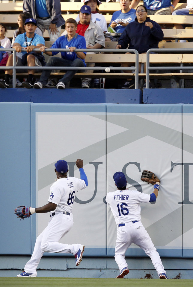 Photo - Los Angeles Dodgers center fielder Andre Ethier (16) and right fielder Yasiel Puig (66) watch the ball bounce over the fence for a ground rule double hit by Colorado Rockies' Justin Morneau in the first inning of a baseball game on Monday, June 16, 2014, in Los Angeles.   (AP Photo/Alex Gallardo)