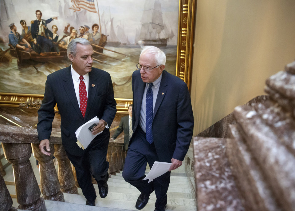 Photo - Senate Veterans' Affairs Committee Chairman Sen. Bernie Sanders, I-Vt., right and House Veterans' Affairs Committee Chairman Rep. Jeff Miller, R-Fla., take the stairs to a news conference on Capitol Hill, in Washington, Monday, July 28, 2014, about a bipartisan deal to improve veterans' health care that would authorize at least $17 billion to fix the health program scandalized by long patient wait times and falsified records covering up delays. (AP Photo/J. Scott Applewhite)