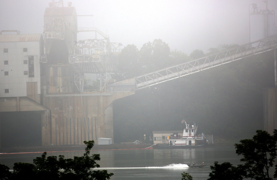 Photo - Cleanup is underway near the Beckjord Power Plant, in New Richmond, Ohio, after an estimated 5,000 to 8,000 gallons of fuel oil spilled into the Ohio River, closing about a 15-mile section of the waterway southeast of Cincinnati, on Tuesday, Aug. 19, 2014. (AP Photo/The Cincinnati Enquirer, Amanda Rossmann)