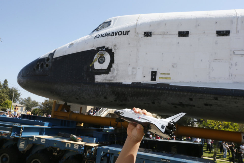 A boy holds a model of the space shuttle Endeavour near the shuttle as it is moved to the California Science Center in Los Angeles on Saturday, Oct. 13, 2012. (AP Photo/Lucy Nicholson, Pool)