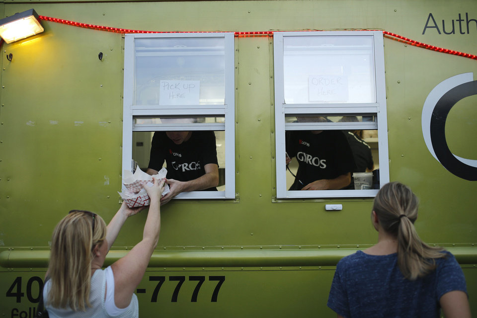 Photo - A person gets their food while another orders at Cafe Bella's truck during H&8th on Hudson between 7th and 8th streets, Friday, September 27, 2013. Photo by Doug Hoke, The Oklahoman