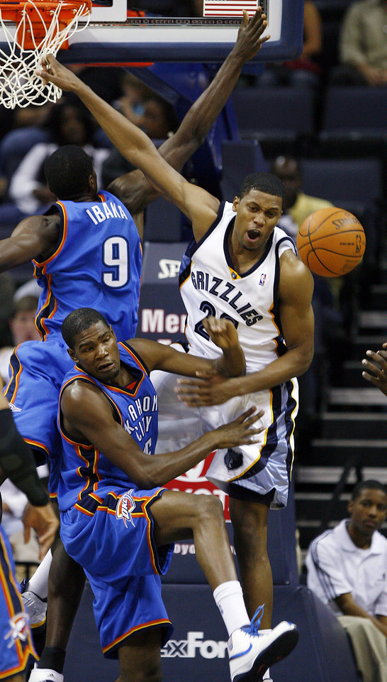 Photo - Memphis Grizzlies forward Rudy Gay (22) gets the ball knocked away by Oklahoma City Thunder's Kevin Durant (35) and Serge Ibaka (9), of the Republic of Congo, during the first half of a preseason NBA basketball game Wednesday, Oct. 7, 2009, in Memphis, Tenn. (AP Photo/Lance Murphey) ORG XMIT: TNLM104