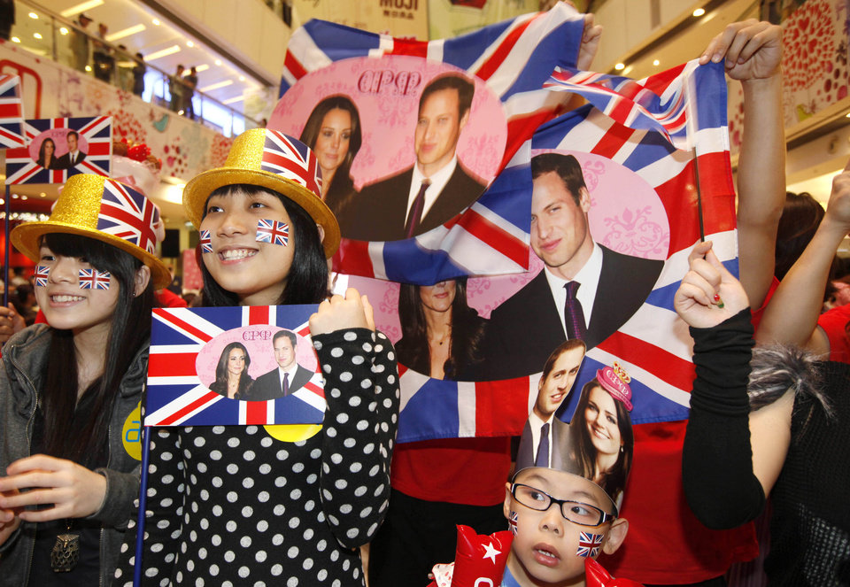 Photo - Hong Kong residents hold British flags with picture of Britain's Prince William and Kate Middleton as they are celebrating the Royal Wedding at a shopping mall in Hong Kong Friday, April 29, 2011.  (AP Photo/Kin Cheung) ORG XMIT: XKC113