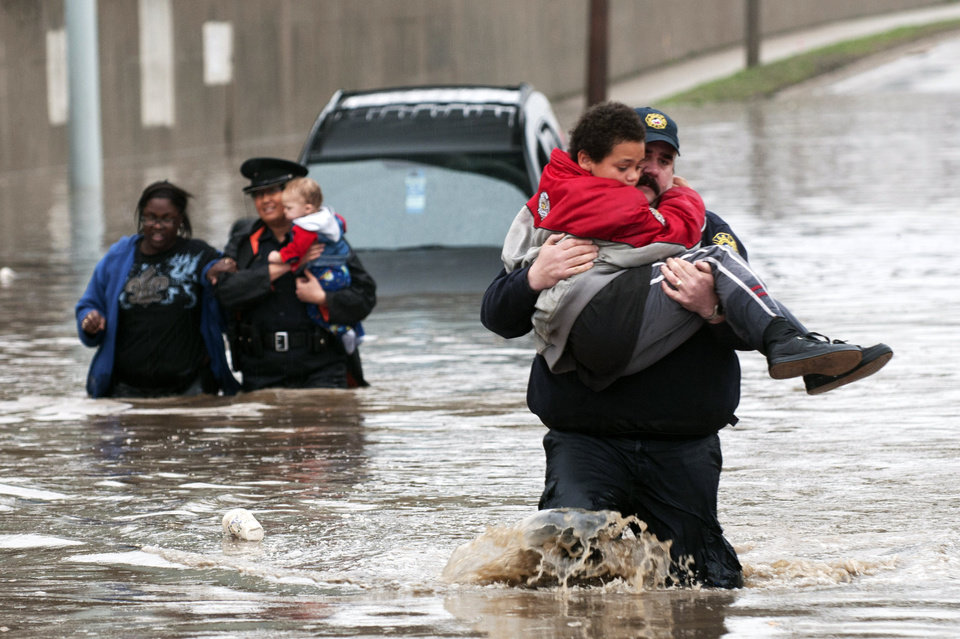 Photo - Firefighter Jason Kelley and police officer Shannon Vandenheuvel carry children from Barbara Jones' partially submerged car  in Grand Rapids, Mich. Thursday, April 18, 2013. Middle America was getting everything nature has to throw at it on Thursday, from snow in the north to tornadoes in the Plains, and with torrential rains causing floods and transportation chaos in several states. (AP Photo/Grand Rapids Press, Chris Clark)