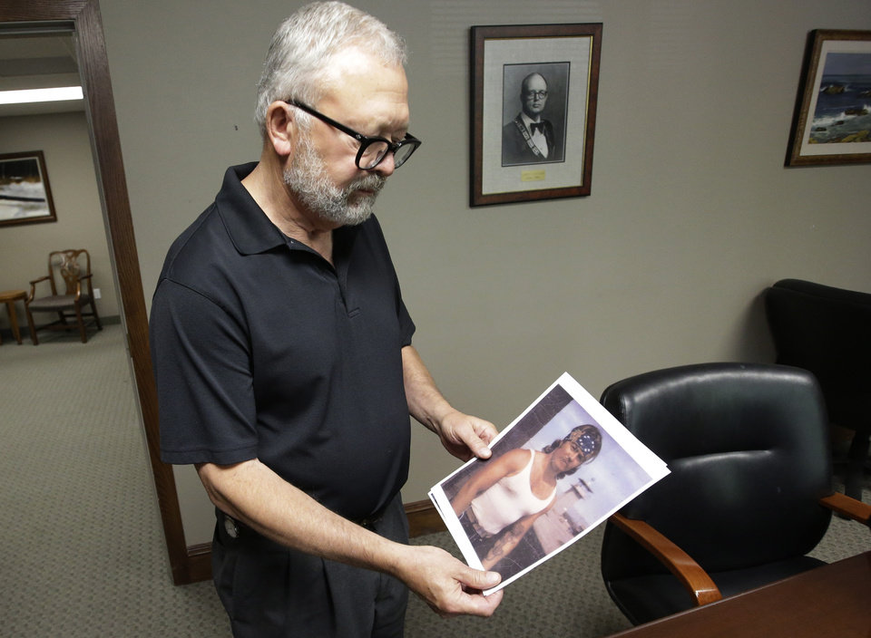 Photo - In this July 16, 2014, photo, Salt Lake City attorney Jesse Trentadue holds a photograph of his brother taken in the early 80's showing his dragon tattoo on his left forearm which fit the description the FBI was circulating of