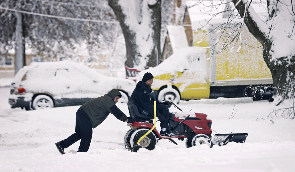 Photo - Victor Jimenez, of Des Moines, Iowa, gets a push from his dad Guillermo Jimenez, left, as they clear snow off a driveway, Thursday, Dec. 20, 2012, in Des Moines, Iowa. The first widespread snowstorm of the season began a slow crawl across the Midwest on Thursday with some areas receiving as much as 15 inches of snow. (AP Photo/Charlie Neibergall)