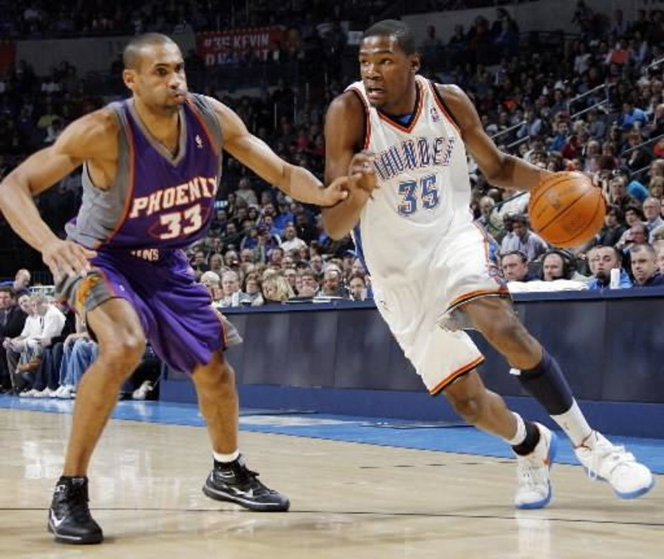 Oklahoma City\'s Kevin Durant (35) drives the ball as Grant Hill (33) of Phoenix defends during the NBA basketball game between the Phoenix Suns and the Oklahoma City Thunder at the Ford Center in Oklahoma City, Tuesday, Feb. 23, 2010. Photo by Nate Billings