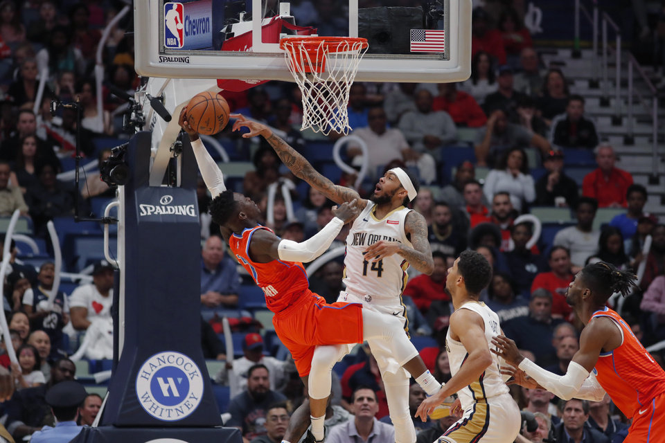 Photo - New Orleans Pelicans forward Brandon Ingram (14) blocks a shot by Oklahoma City Thunder guard Dennis Schroder (17) in the second half of an NBA basketball game in New Orleans, Sunday, Dec. 1, 2019. The Thunder won 107-104. (AP Photo/Gerald Herbert)