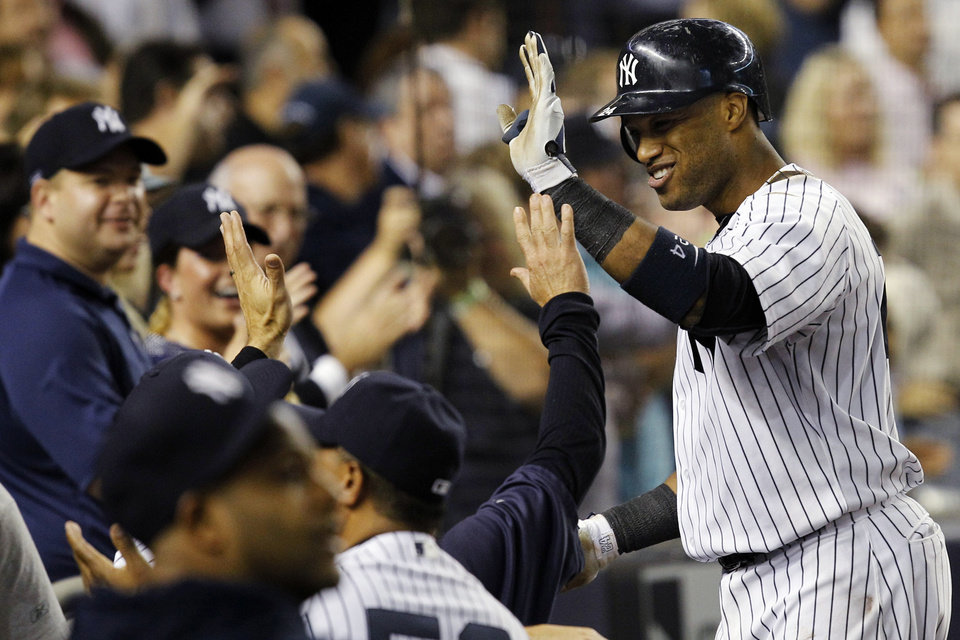Photo -   New York Yankees' Robinson Cano is greeted at the dugout steps after hitting a fifth-inning, two-run home run against the Boston Red Sox during their baseball game at Yankee Stadium in New York, Wednesday, Oct. 3, 2012. (AP Photo/Kathy Willens)