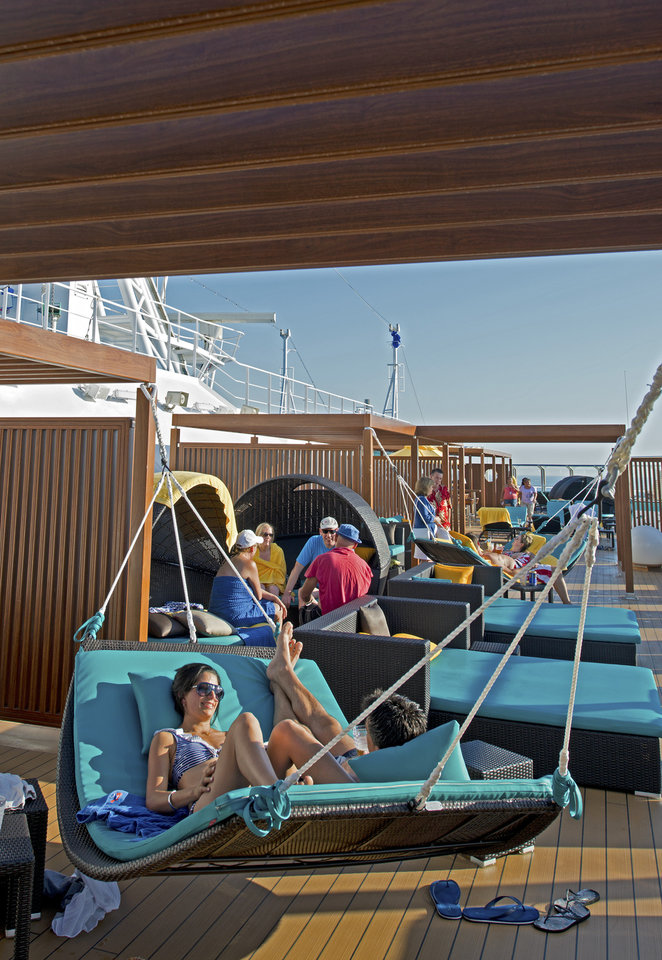 "In this June 17, 2012 photo provided by Carnival Cruise Lines, vacationers aboard the Carnival Breeze relax at Serenity, an adults-only area offering plush chaise lounges and chairs, whirlpools, and a dining area with salads, wraps and other light fare. Multi-generational groups are a growing segment of cruise passengers. To accommodate the diverse needs of old and young passengers, ships are expanding areas for youth activities while at the same time creating more adult-only pools and quiet areas where adult passengers can nap, sun, or read a book. Carnival ships call these areas ""Serenity Spaces.""  (AP Photo/Carnival Cruise Lines, Andy Newman)"