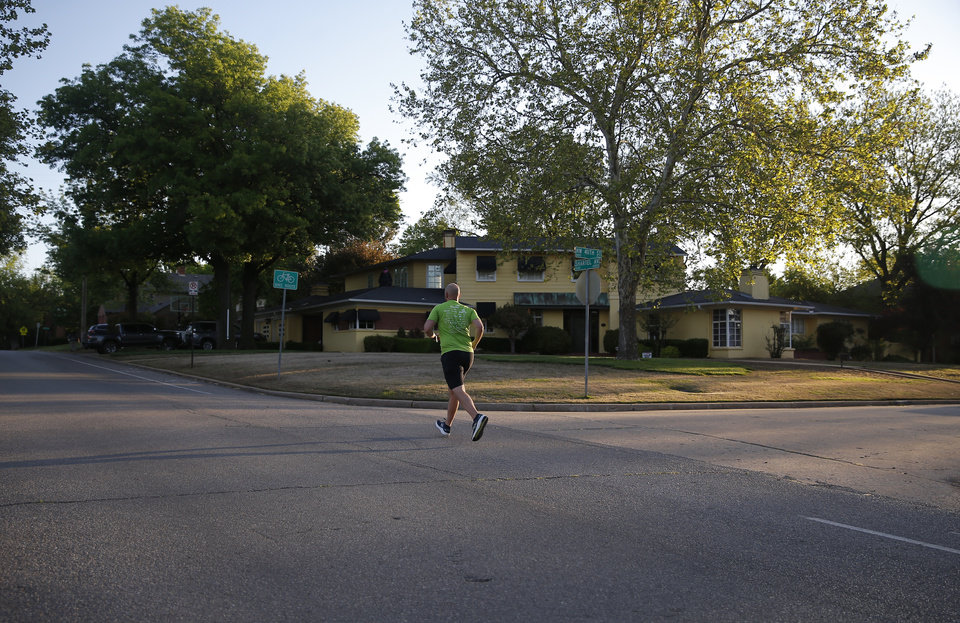Photo - A runner runs up gorilla hill on the route of  the Oklahoma City Memorial Marathon in Oklahoma City,  Sunday, April 26, 2020.  The 20th Oklahoma City Memorial Marathon was delayed until October because of Covid-19. [Sarah Phipps/The Oklahoman]
