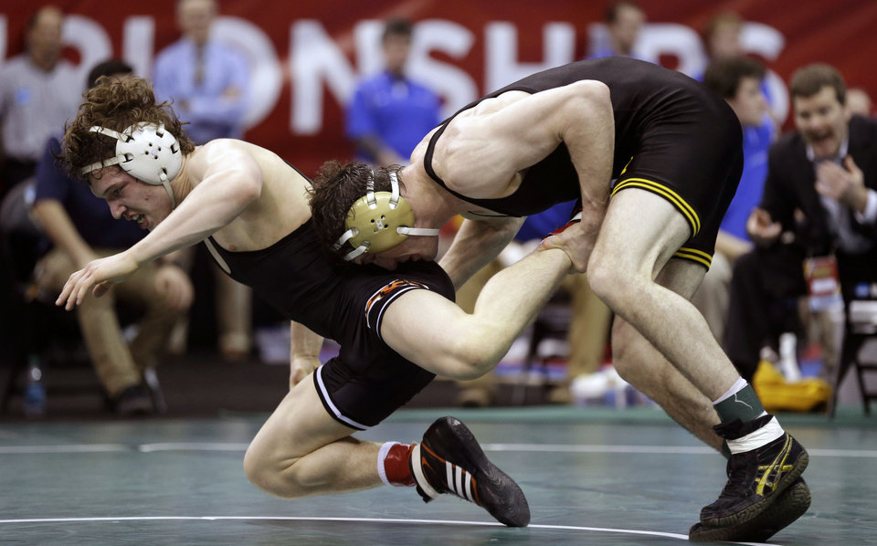Iowa\'s Derek St. John, right, tries to take down Oklahoma State\'s Alex Dieringer during their 157-pound semifinal round match at the NCAA Division I wrestling championships on Friday, March 22, 2013, in Des Moines, Iowa. (AP Photo/Charlie Neibergall)