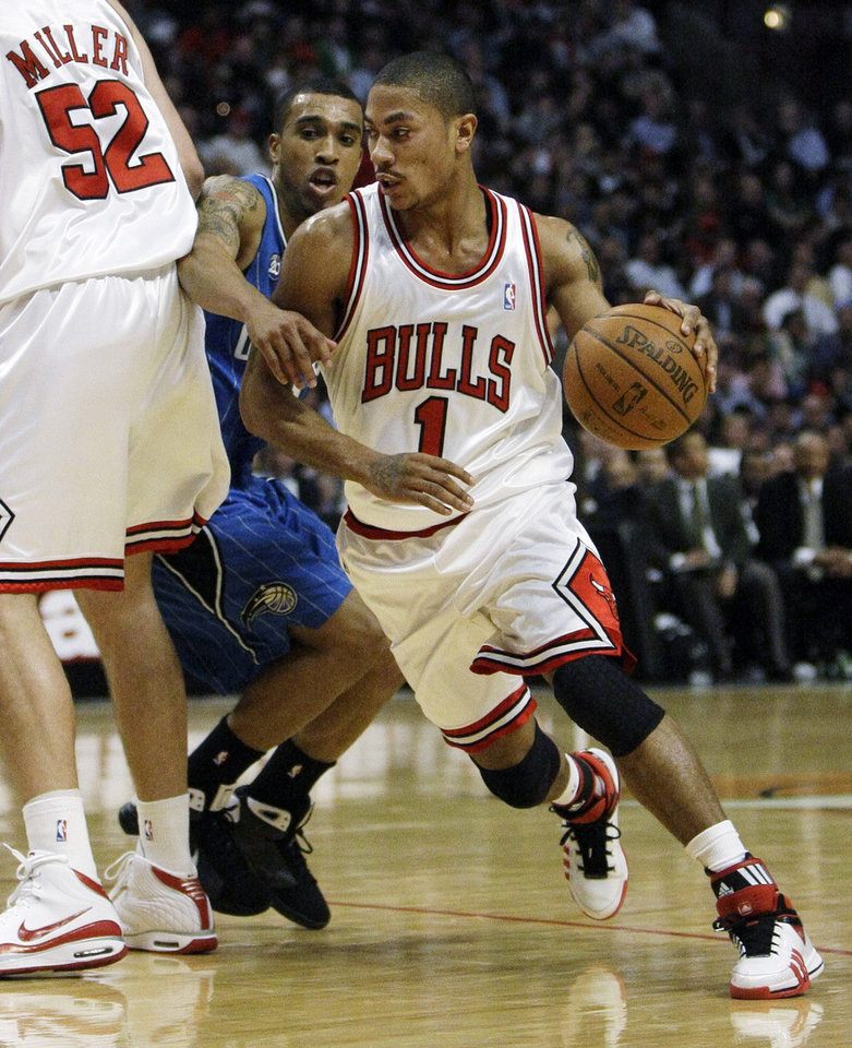 Photo - Chicago Bulls guard Derrick Rose, right, loses his defender Orlando Magic guard Courtney Lee off a pick by center Brad Miller, left, during the second half of their NBA basketball game in Chicago, Tuesday, Feb. 24, 2009. Rose led the Bulls to a 120-102 win with 22 points. (AP Photo/Charles Rex Arbogast) ORG XMIT: CXA105