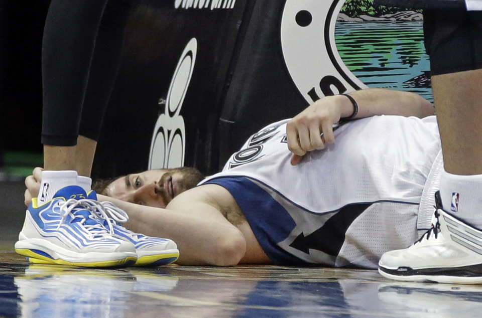 Photo - Minnesota Timberwolves' Kevin Love lies on the court after falling and hitting his head after he was fouled by Los Angeles Lakers' Robert Sacre while attempting a shot in the second half of an NBA basketball game, Tuesday, Feb. 4, 2014, in Minneapolis. Love was attended to but continued in the game. The Timberwolves won 109-99. Love led his team with 31 points and 17 rebounds.  (AP Photo/Jim Mone)
