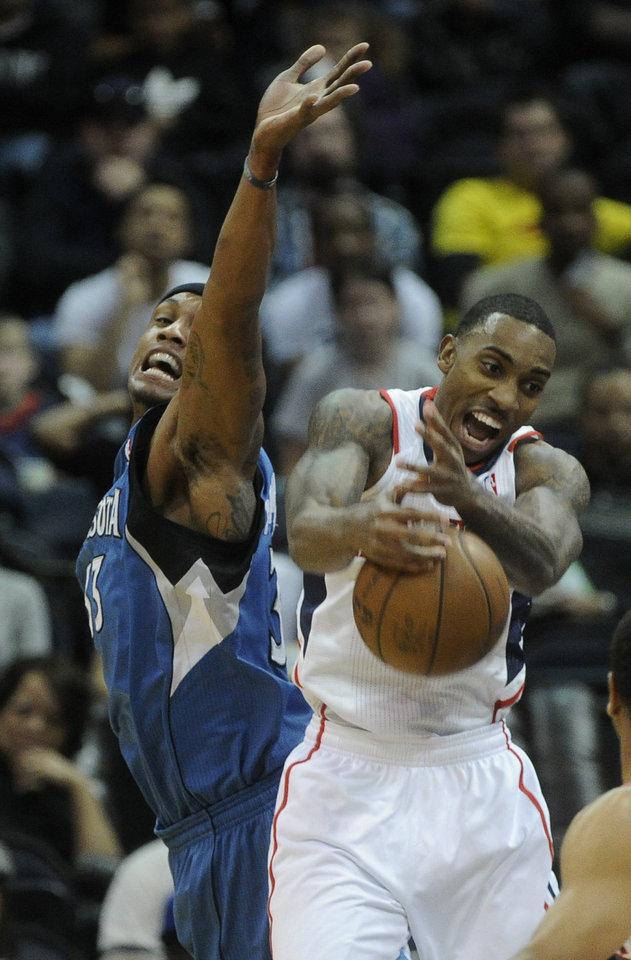 Atlanta Hawks point guard Jeff Teague (0), right, grabs a rebound in front of Minnesota Timberwolves forward Dante Cunningham (33) during the first half on an NBA basketball game in Atlanta, Monday, Jan. 21, 2013. (AP Photo/John Amis)