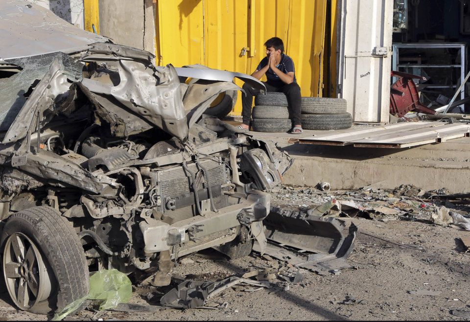 Photo - A man sits in front of his shop that was damaged in a Saturday car bomb attack near a Kebab restaurant, in the mainly Shiite Habibiya neighborhood of Baghdad, Iraq, Sunday, May 11, 2014. A series of bombings on Saturday in Iraq killed and wounded scores of people, a day after army shelling killed many civilians and gunmen in the militant-held city of Fallujah, authorities said. (AP Photo/Karim Kadim)