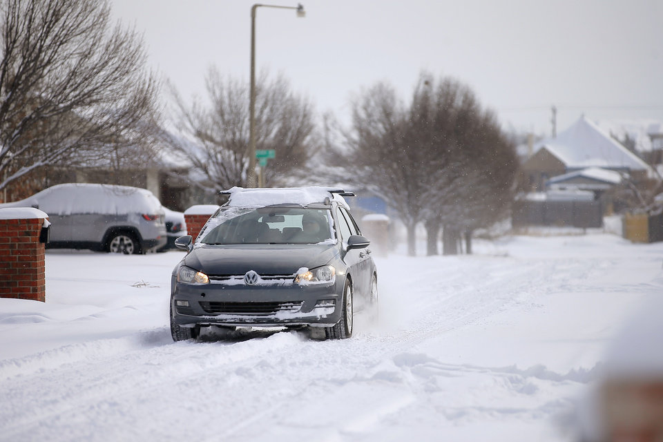 Photo - A car drives along a neighborhood street  in northwest Oklahoma City after a winter storm dropped another layer of snow in Oklahoma City, Wednesday, Feb. 17, 2021. [Bryan Terry/The Oklahoman]