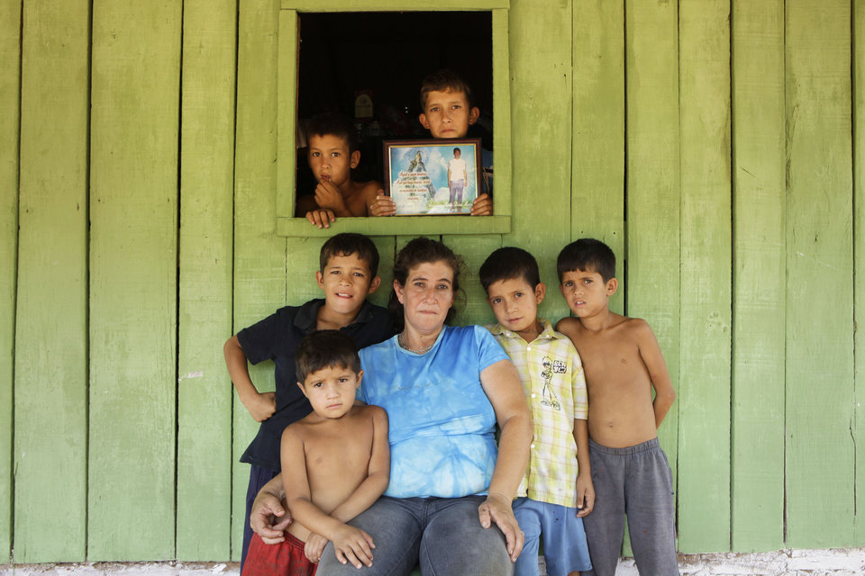 "In this Nov. 7, 2012 photo, Juana Evangelista Martinez, 42, poses for a portrait with her sons, Eulalio, 5, resting on her lap, Christian, 10, in window left, Gabriel, 10, middle row left, Ricardo, 12, in window right, Arnaldo, 9, second from right, and Fabio, 8, right, in the Yvy Pyta settlement near Curuguaty, Paraguay. Martinez 's husband, Arnaldo Ruiz Diaz, was killed during the ""Massacre of Curuguaty"" on June 15 when negotiations between farmers occupying a rich politician's land ended with a barrage of bullets that killed 11 farmers and 6 police officers. (AP Photo/Jorge Saenz)"