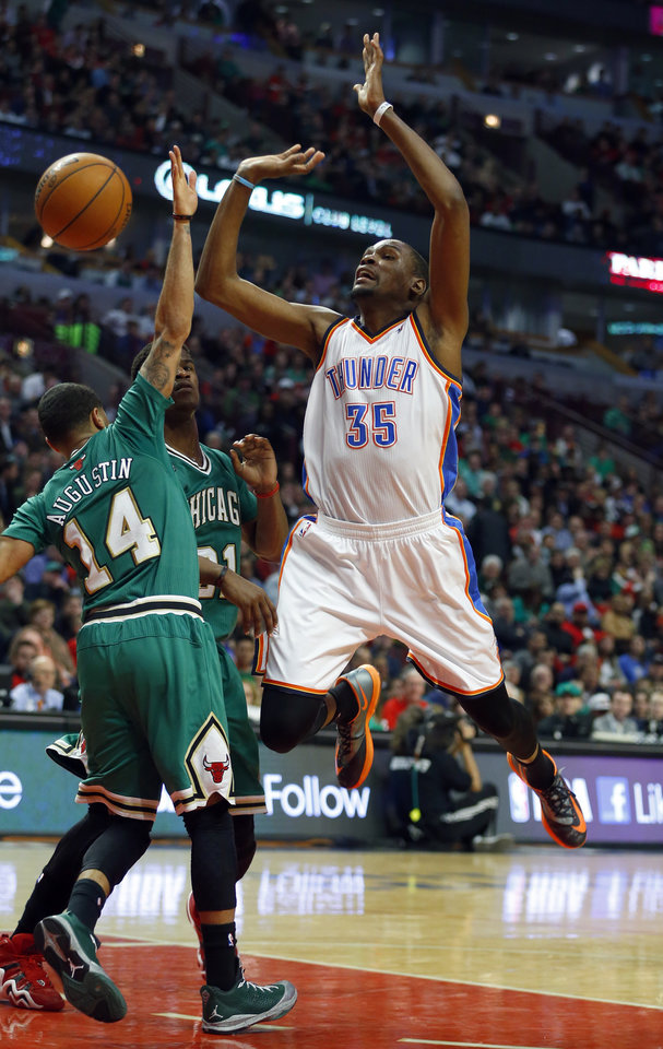 Photo - Oklahoma City Thunder forward Kevin Durant (35) has the ball stripped from him by Chicago Bulls guard D.J. Augustin (14) during the first half of an NBA basketball Monday, March 17, 2014, in Chicago.  (AP Photo/Jeff Haynes)