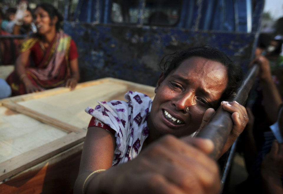 A Bangladeshi woman weeps as she sits next to the coffin of a relative who died in a building that collapsed Wednesday in Savar, near Dhaka, Bangladesh, Sunday, April 28, 2013. A fire broke out late Sunday in the wreckage of the garment factory that collapsed last week in Bangladesh killing hundreds, with smoke pouring from the piles of shattered concrete and some of the rescue efforts forced to stop.(AP Photo/Kevin Frayer)