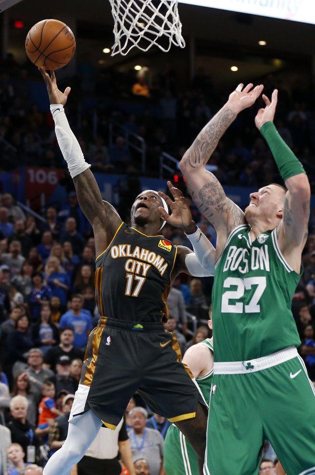 Photo - Oklahoma City's Dennis Schroder (17) shoots next to Daniel Theis (27) in the fourth quarter during an NBA basketball game between the Oklahoma City Thunder and the Boston Celtics at Chesapeake Energy Arena in Oklahoma City, Sunday, Feb. 9, 2020. Boston won 112-111. [Nate Billings/The Oklahoman]