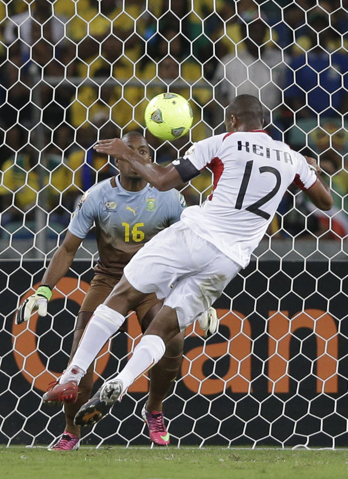 Photo - Mali's captain Seydou Keita heads the ball past South Africa's goalkeeper Itumeleng Khune to score, in their African Cup of Nations quarterfinal soccer match, at Moses Mabhida Stadium in Durban, South Africa, Saturday, Feb. 2, 2013. (AP Photo/Rebecca Blackwell)