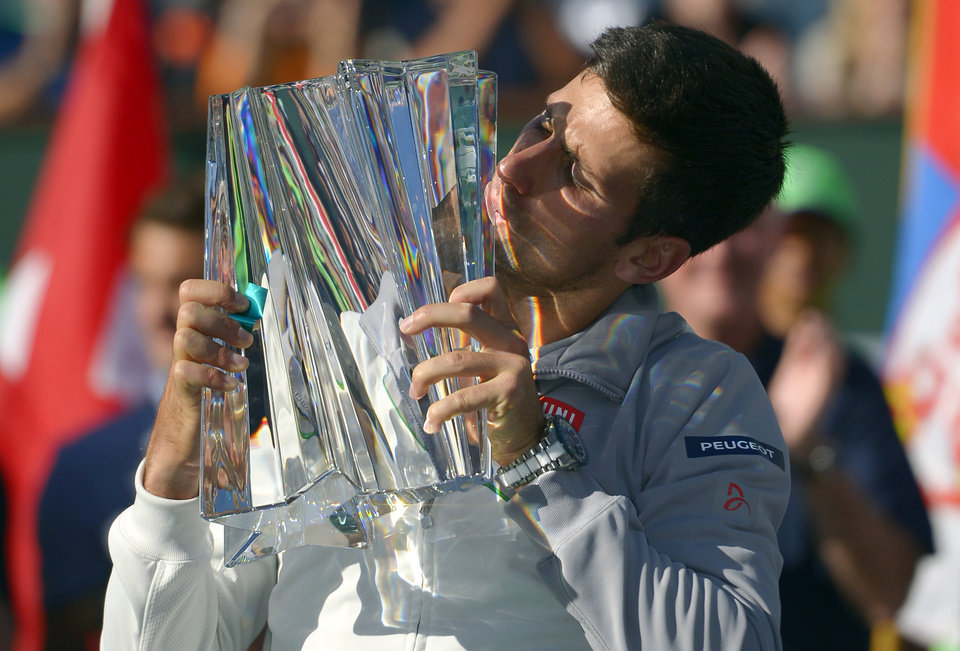 Photo - Novak Djokovic, of Serbia, kisses the trophy after he beat Roger Federer, of Switzerland, 3-6, 6-3, 7-6 to win the final match of the BNP Paribas Open tennis tournament, Sunday, March 16, 2014, in Indian Wells, Calif. (AP Photo/Mark J. Terrill)