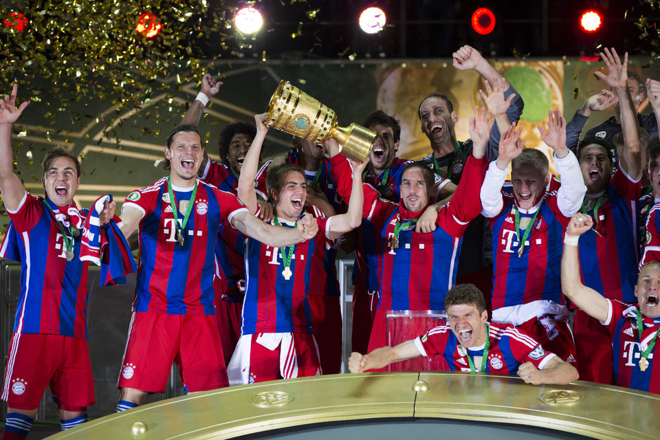 Photo - Bayern's Philipp Lahm holds the trophy as the team of FC Bayern Munich  celebrates after winning the German Soccer Cup Final between FC Bayern Munich and Borussia Dortmund at the Olympic Stadium in Berlin, Germany, Saturday, May 17, 2014. (AP Photo/Gero Breloer)