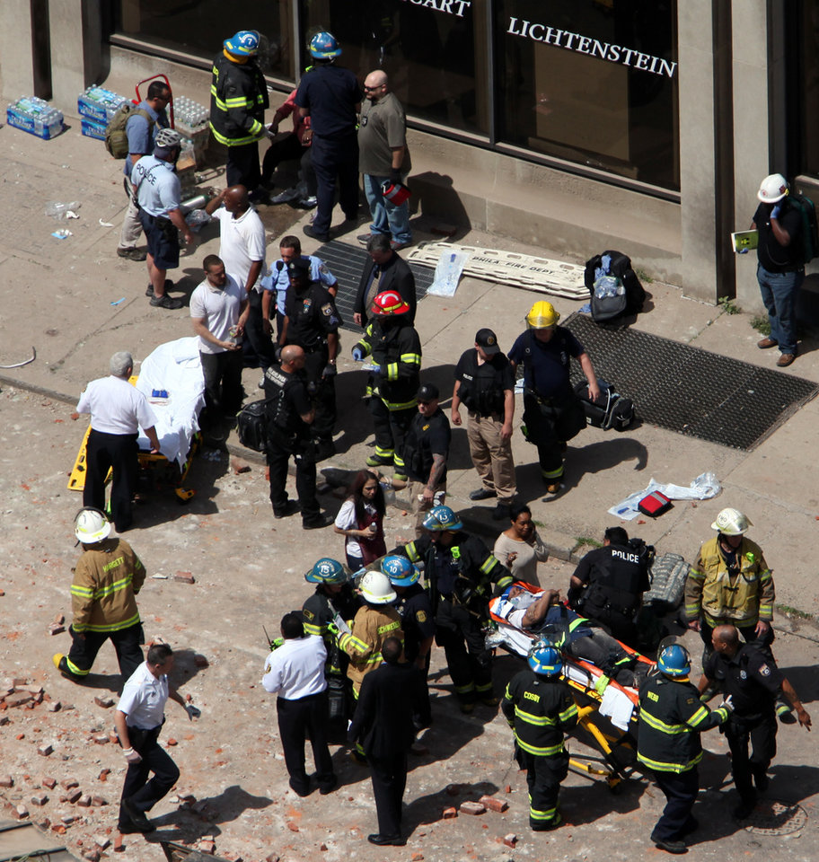 Photo - Rescue personnel evacuate an injured person from the scene of a building collapse in downtown Philadelphia, Wednesday, June 5, 2013.  A four-story building being demolished collapsed Wednesday on the edge of downtown, injuring 12 people and trapping two others, the fire commissioner said. Rescue crews were trying to extricate the two people who were trapped, city Fire Commissioner Lloyd Ayers said. The dozen people who were injured were taken to hospitals with minor injuries, according to Ayers. (AP Photo/Jacqueline Larma)