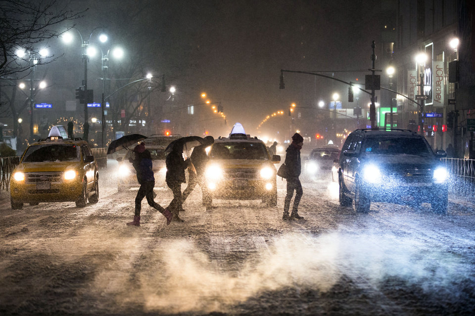 Photo - Pedestrians cross 34th Street and 6th Avenue under falling snow in Herald Square, Thursday, Jan. 2, 2014, in New York. The storm is expected to bring snow, stiff winds and punishing cold into the Northeast. (AP Photo/John Minchillo)