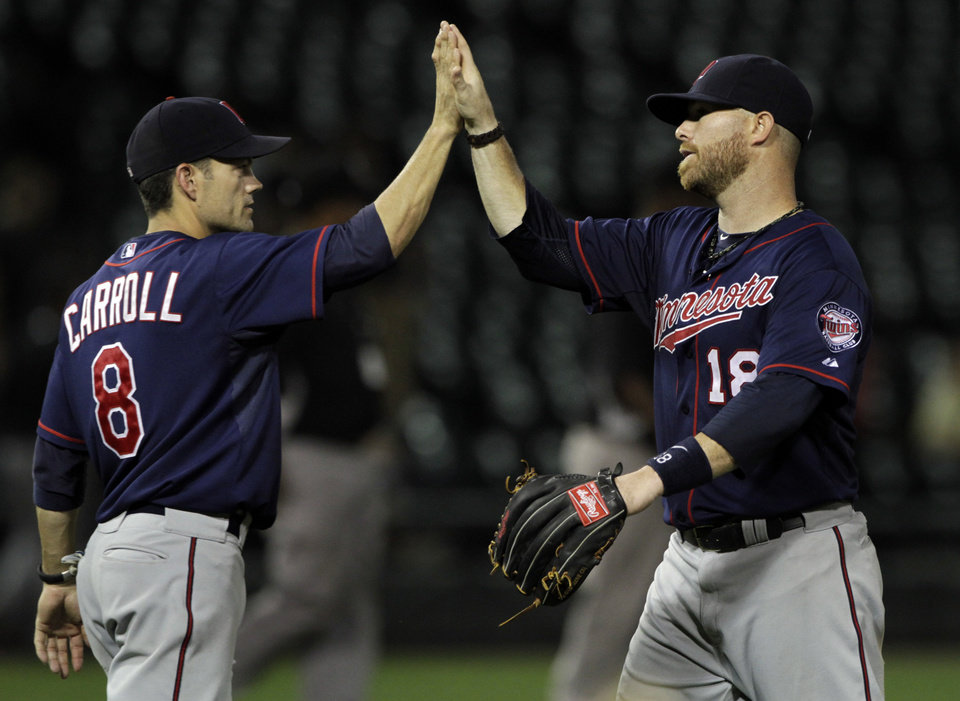 Photo -   Minnesota Twins' Jamey Carroll (left) and Josh Willingham (right) congratulate each other after beating the Chicago White Sox 18-9. (AP Photo/John Smierciak)