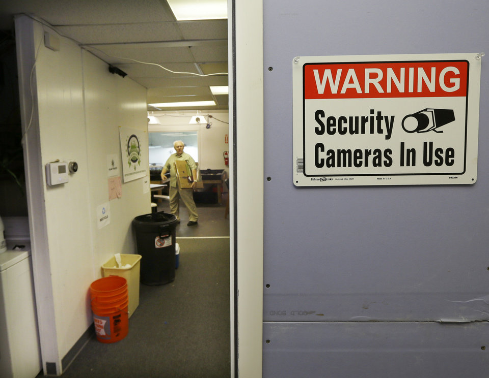 Photo - This July 8, 2014, photo shows a sign warning about the use of security cameras at Sea of Green Farms, a recreational pot grower and processor in Seattle. Multiple cameras and alarms are used to protect the high-dollar crop. (AP Photo/Ted S. Warren)