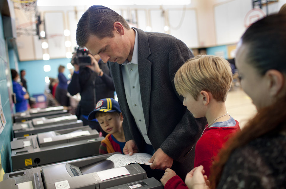 Photo -   New Mexico Democratic U.S. Senate candidate, Rep. Martin Heinrich, inserts his ballot into a machine Tuesday, Nov. 6, 2012, at Bandelier Elementary School in Albuquerque, NM while his sons Micah, 6, left, and Carter, 9, right, watch. (AP Photo/Craig Fritz)