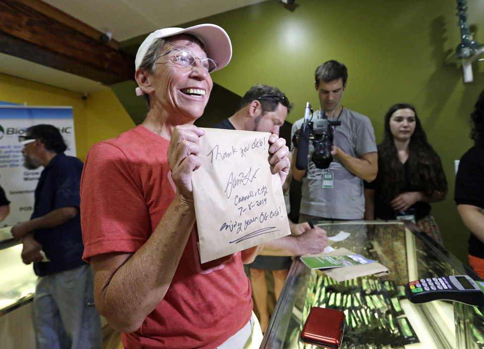 Photo - Deb Greene, the store's first customer, displays her purchase of legal recreational marijuana at Cannabis City Tuesday, July 8, 2014, in Seattle. She waited in line since Monday afternoon for the store to open. Washington on Tuesday became the second state to allow people to buy marijuana legally in the U.S. without a doctor's note as eager customers who lined up outside stores made their purchases and savored the moment. (AP Photo/Elaine Thompson, Pool)