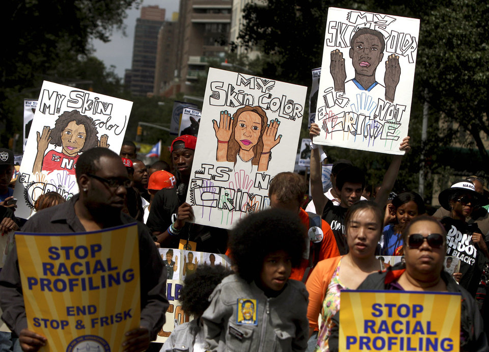 Photo - FILE - In this June 17, 2012 file photo, demonstrators hold signs during a silent march in New York to end the New York City Police Department's