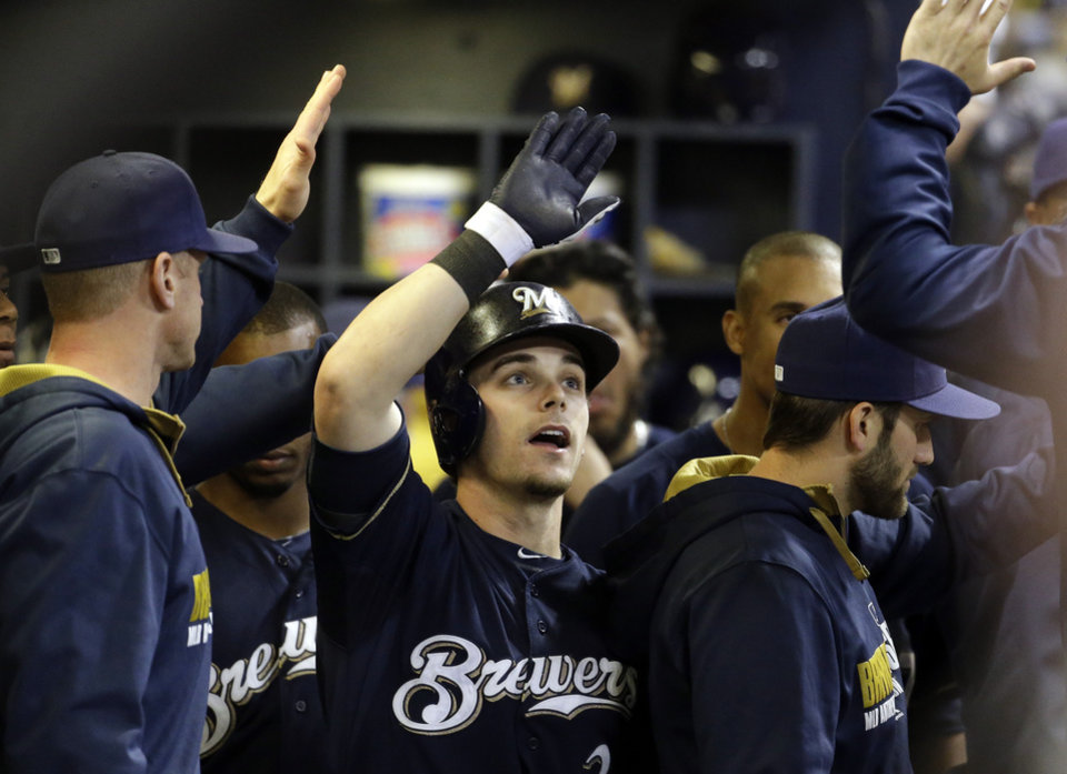 Photo - Milwaukee Brewers' Scooter Gennett is congratulated after hitting a home run during the fifth inning of a baseball game against the San Diego Padres on Tuesday, April 22, 2014, in Milwaukee. (AP Photo/Morry Gash)