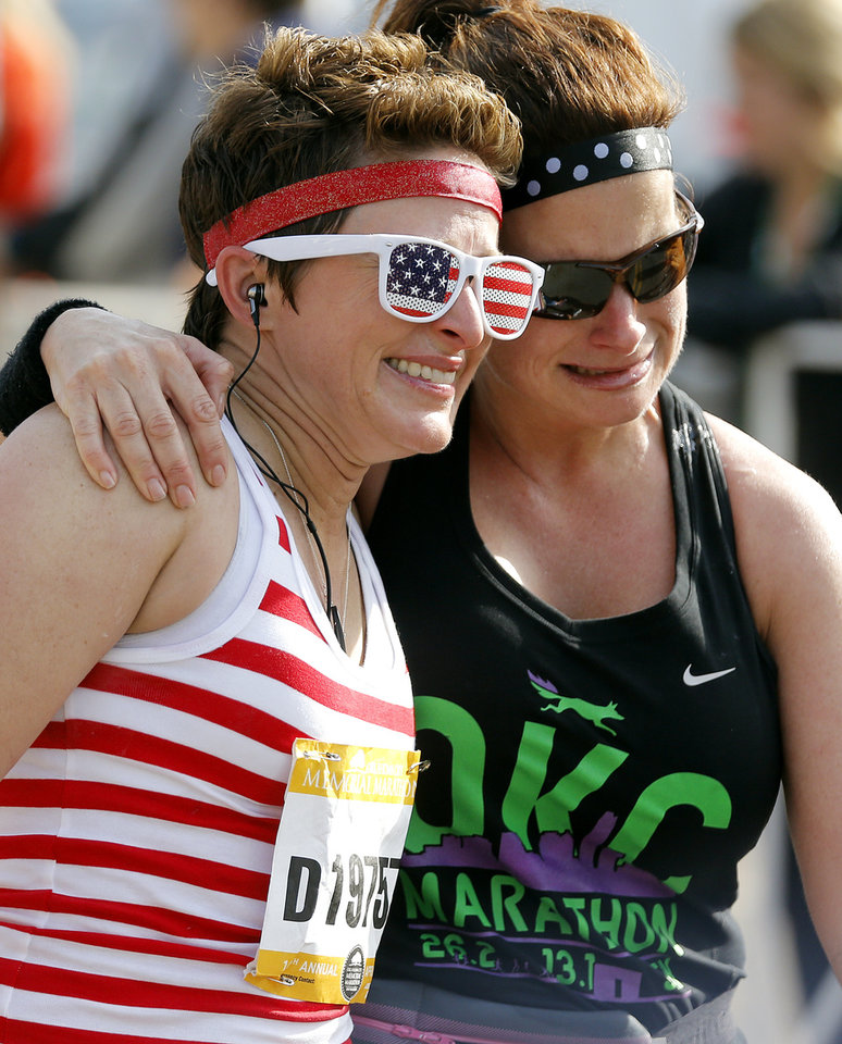 Photo - Melissa Marks, left, and Tracy Martens hug each other as they finish the half marathon during the Oklahoma Memorial Marathon in Oklahoma City, Okla. on Sunday, April 24, 2016.   Photo by Chris Landsberger, The Oklahoman